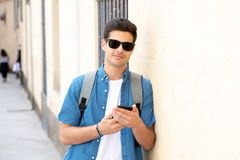 Happy young student male texting on his smart phone in modern city. Young happy student man in jeans denim clothes wearing sunglasses texting on his smart mobile Royalty Free Stock Photo