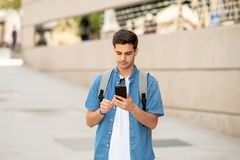 Happy young student male texting on his smart phone in modern city. Young happy student man in jeans denim clothes wearing sunglasses texting on his smart mobile Royalty Free Stock Photography