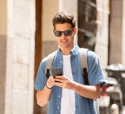 Happy young student male texting on his smart phone in modern ci. Young happy student man in jeans denim clothes wearing sunglasses texting on his smart mobile Stock Photos