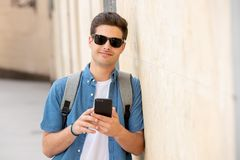 Happy young student male texting on his smart phone in modern city stock photography