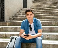 Happy young student male texting on his smart phone in modern ci. Young happy student man in jeans denim clothes wearing sunglasses texting on his smart mobile Stock Image