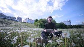 Young happy student using tablet in the park, lying on the grass in dandelions, smiling and laughing. stock video