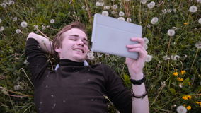 Young happy student using tablet in the park, lying on the grass in dandelions, smiling and laughing. Young happy student using tablet in the park, lying on the stock video footage