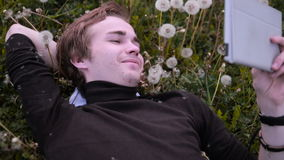 Young happy student using tablet in the park, lying on the grass in dandelions, smiling and laughing. stock video footage