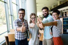 Young happy students sitting in library Royalty Free Stock Image