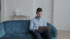 Young happy stylish guy in blue shirt chatting with his friends. He smiles and typing on laptop using messaging stock video footage