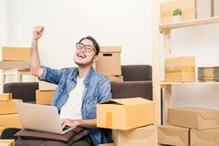 Young happy success Asian man with his hand lift up stock image