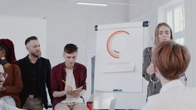 Young happy successful blonde business woman leading team discussion at modern light office meeting slow motion RED EPIC. Multiethnic smiling colleagues listen stock video footage