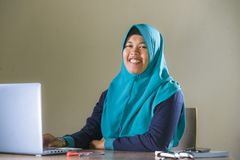 Young happy and successful Muslim student woman in traditional Islam hijab head scarf working on desk studying with laptop royalty free stock photos