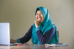 Young happy and successful Muslim student woman in traditional Islam hijab head scarf working on desk studying with laptop stock image
