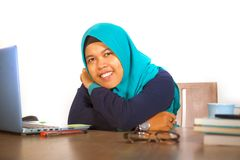 Young happy and successful Muslim student woman in traditional Islam hijab head scarf working on desk studying with laptop. Computer and textbook smiling royalty free stock photo