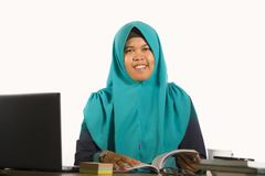 Young happy and successful Muslim student woman in traditional Islam hijab head scarf working on desk studying with laptop stock photo