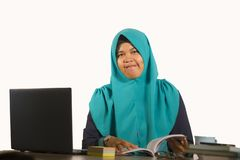 Young happy and successful Muslim student woman in traditional Islam hijab head scarf working on desk studying with laptop royalty free stock image