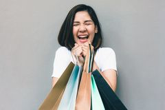 Young happy summer shopping asian woman with shopping bags on grey background at copy space. Beautiful young mixed race asian woman. Chinese asian woman royalty free stock photos