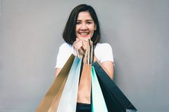 Young happy summer shopping asian woman with shopping bags on grey background at copy space. Beautiful young mixed race asian woman. Chinese asian woman stock image