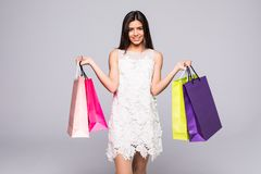 Young happy summer shopping woman with shopping bags on grey background Stock Image