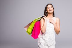 Young happy summer shopping woman with shopping bags on grey background Royalty Free Stock Image