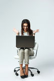 Young happy surprised businesswoman with laptop sitting on chair Royalty Free Stock Image