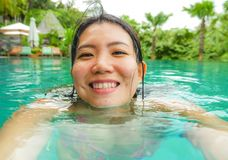 Young happy and sweet Asian Chinese woman swimming in tropical resort pool taking selfie portrait picture with mobile phone. Smiling excited and cheerful stock photo