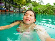 Young happy and sweet Asian Korean woman swimming in tropical resort pool taking selfie portrait picture with mobile phone smiling. Excited and cheerful stock image
