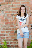 Young happy teen girl standing at brick wall background copyspace Stock Photos