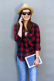 Young happy teen girl using a smart phone, tablet over wall in t Stock Images