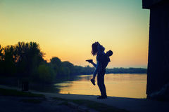 Young happy teenage couple having fun beside river at spring sun stock image