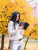 Young happy teenage girl using her tablet and listening to music in autumn city park. Fall life-style picture Stock Photos