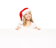 Young and happy teenager in a Christmas hat holding a banner. Young and attractive teenager girl with a blank billboard isolated on white background Stock Image