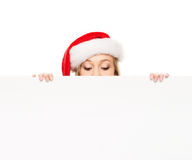 Young and happy teenager in a Christmas hat holding a banner. Young and attractive teenager girl with a blank billboard isolated on white background Royalty Free Stock Photography