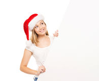 Young and happy teenager in a Christmas hat holding a banner. Young and attractive teenager girl with a blank billboard isolated on white background Royalty Free Stock Photo