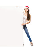 Young and happy teenager in a Christmas hat holding a banner. Young and attractive teenager girl with a blank billboard  on white background Stock Photography