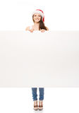 Young and happy teenager in a Christmas hat holding a banner. Young and attractive teenager girl with a blank billboard  on white background Stock Images