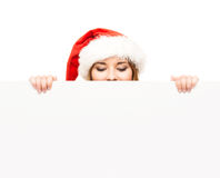 Young and happy teenager in a Christmas hat holding a banner. Young and attractive teenager girl with a blank billboard  on white background Stock Photos