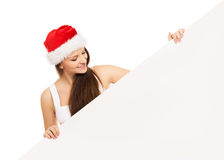 Young and happy teenager in a Christmas hat holding a banner. Young and attractive teenager girl with a blank billboard  on white background Royalty Free Stock Photo