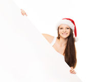 Young and happy teenager in a Christmas hat holding a banner. Young and attractive teenager girl with a blank billboard  on white background Royalty Free Stock Photography