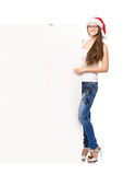 Young and happy teenager in a Christmas hat holding a banner. Young and attractive teenager girl with a blank billboard  on white background Royalty Free Stock Photos