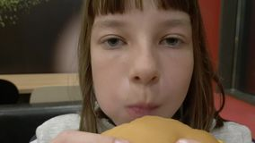 Young happy teenager eating tasty hamburger in fast food restaurant. Teen girl eating french fries for dinner at fast. Food cafe stock video footage