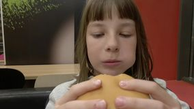 Young happy teenager eating tasty hamburger in fast food restaurant. Teen girl eating french fries for dinner at fast stock footage