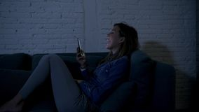 Young happy teenager girl or woman on her 20s lying on home couch late night happy using internet social media on mobile phone stock video footage