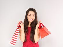 Young happy toothy smiling woman with shopping bags. Happy New Year Holidays royalty free stock images