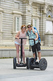 Young happy tourist couple riding segway enjoying city tour in Madrid palace in Spain having fun driving together Stock Image