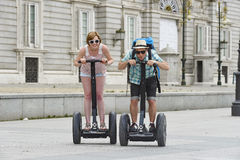 Young happy tourist couple riding segway enjoying city tour in Madrid palace in Spain having fun driving together Royalty Free Stock Photography