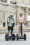 Young happy tourist couple riding segway enjoying city tour in Madrid palace in Spain having fun driving together Stock Photography