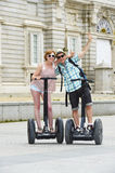 Young happy tourist couple riding segway enjoying city tour in Madrid palace in Spain having fun driving together Stock Photos