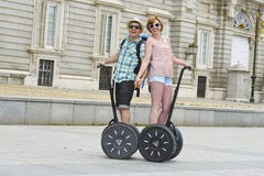 Young happy tourist couple riding segway enjoying city tour in Madrid palace in Spain having fun driving together Royalty Free Stock Images