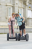 Young happy tourist couple riding segway enjoying city tour in Madrid palace in Spain having fun driving together Stock Images
