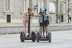 Young happy tourist couple riding segway enjoying city tour in Madrid palace in Spain having fun driving together Royalty Free Stock Photos