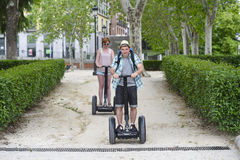 Young happy tourist couple riding segway enjoying city tour in Madrid park in Spain together Stock Photography