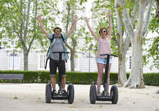 Young happy tourist couple riding segway enjoying city tour in Madrid park in Spain together royalty free stock photo